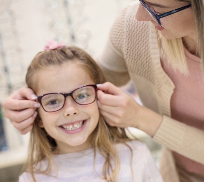 Optician with young girl during eyeglass fitting