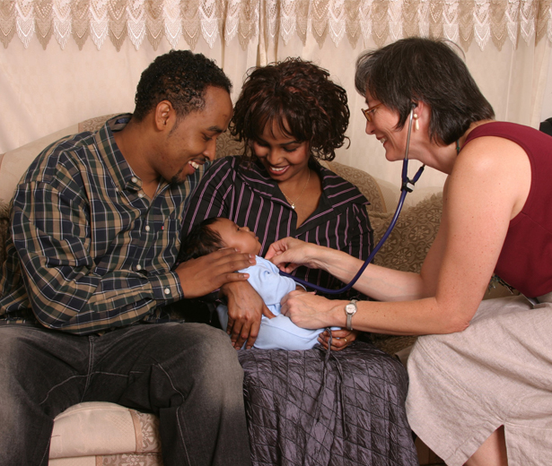 Black couple holding their newborn on the couch while an Allina Home Health nurse listens to the baby's heart.