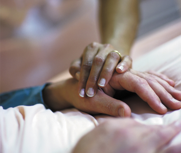 Comforting hand on a patient's hand in a hospice bed.