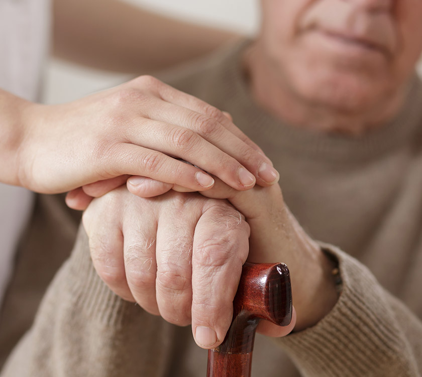 Health care provider holds the hand of a senior man who is holding a cane.